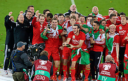 CARDIFF, WALES - Tuesday, October 13, 2015: Wales' Gareth Bale and the squad celebrate after qualifying for the finals following a 2-0 victory over Andorra during the UEFA Euro 2016 qualifying Group B match at the Cardiff City Stadium. Paul Harris, sports science coach Adam Owen, Ronan Kavanagh, goalkeeper Owain Fon Williams, Sam Vokes, Ben Davies,m sport psychologist Ian Mitchall, James Chester, Neil Taylor, James Collins, Joe Allen, Jonathan Williams, Emyr Huws. (Pic by Paul Currie/Propaganda)