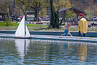 A father and daughter sail a model sailboat in Seattle