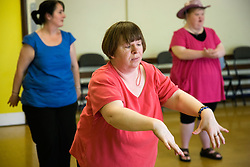 Day Service users with learning disability taking part in dance class with Care Assistant joining in the activity,