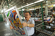 Eztu Glass founder and CEO Brian Yaputra examines a small stained glass window at his company's factory in Tangerang, near Jakarta, Indonesia, on July 2, 2015.