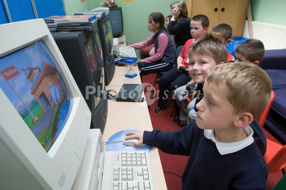Group of primary school children using computers in classroom,