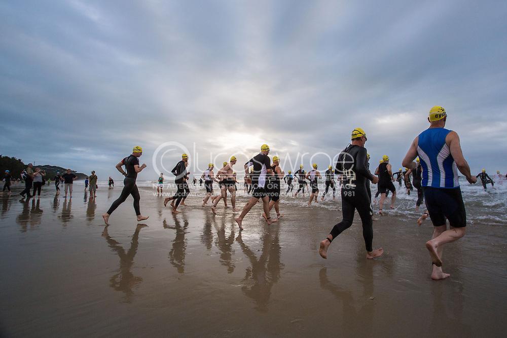 Age Group Competitors enter the water at the swim start, June 1, 2014 - TRIATHLON : Coral Coast 5150 Triathlon, Cairns Airport Adventure Festival, Four Mile Beach, Port Douglas, Queensland, Australia. Credit: Lucas Wroe