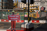 Real construction workers in the background and a scaled human workman figure who warns pedestrians to stay on established footpath, and not wander into construction site roadways during street improvements in Victoria, central London.