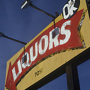 "Vintage, colorful painted sign reading ""Liquors, OK"" near Watsonville, CA. Looking upward against dark blue sky."
