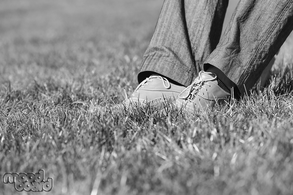 Black and white photo of businessman foot on the grass