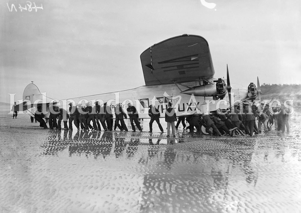 'Faith in Australia' aeroplane being pulled along Portmarnock Strand, 27 July 1933.<br /> Flight Lieutenant and owner of the plane was Charles Ulm, who also co-piloted the 1928 Southern Cross flight across the Pacific with Sir Charles Kingsford Smith. <br /> (Part of the Independent Newspapers Ireland/NLI Collection)