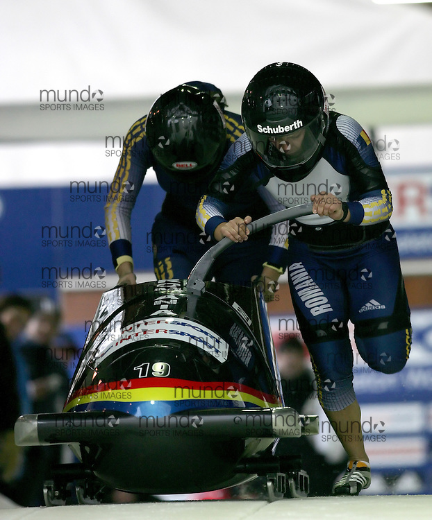 (November 21, 2009) Carmen Radenovic (front) and Alina Vera Saving of Romania Christina Hengster (front) and Inga Versen of Austria push in the first run en route to a 21st place finish at  the Federation Internationale de Bobsleigh et de Togogganing (FIBT) two-man men's bobsled World Cup race at the Olympic Sports Complex in Lake Placid, New York.