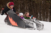 """Once the official Cardboard Sled Derby was over the """"girls"""" decided to take a spin in the """"boys will be boys"""" Speed Racer built by Ty and Caleb Bartlett.  For Avy Bartlett, Abby Jarvi and Mykynzy Bartlett is was a wild ride with a little extra push from Michele Loyer.  (Karen Bobotas/for the Laconia Daily Sun)"""