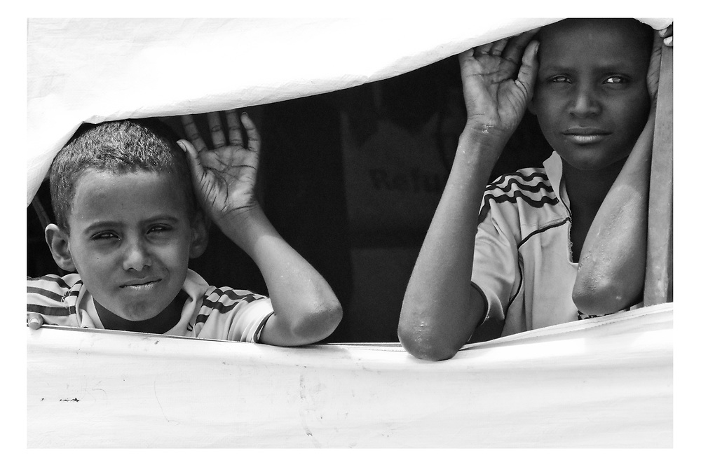 Two young boys look from the windo of his temporary shelter in Asaita Refugee Camp, Afar, Ethiopia 2016
