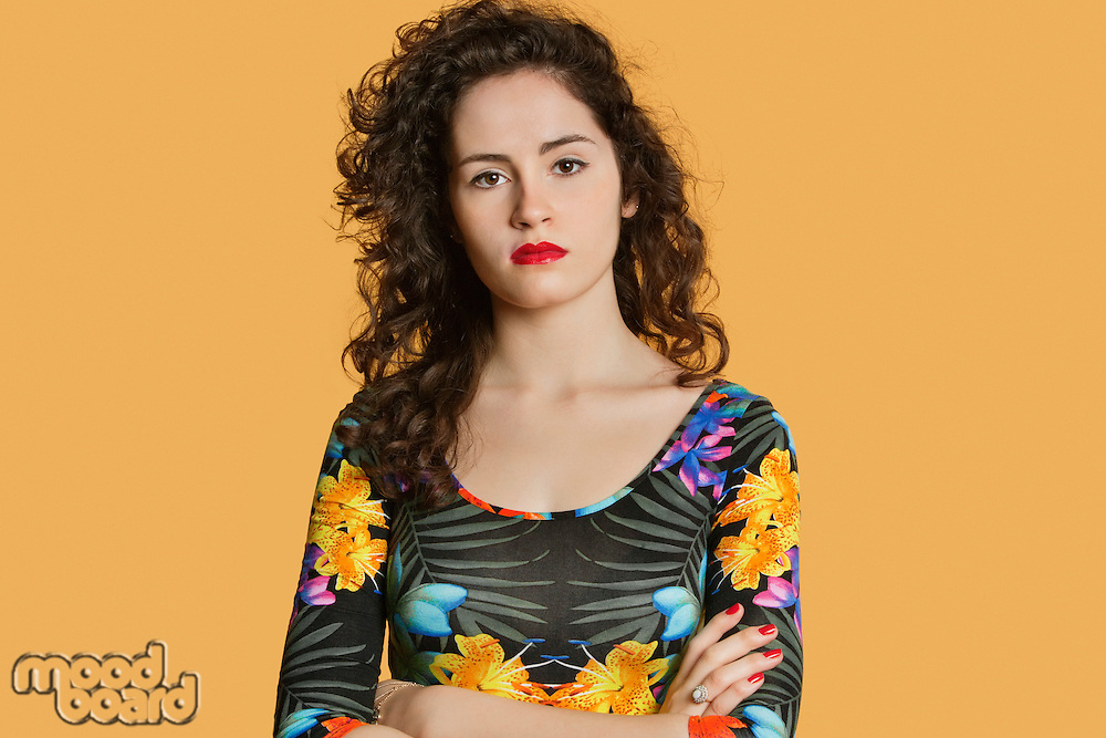 Portrait of a confident young woman with arms crossed over colored background