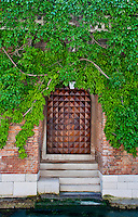 Door on a canal with a beautiful green ivy covered wall in Venice, Italy.