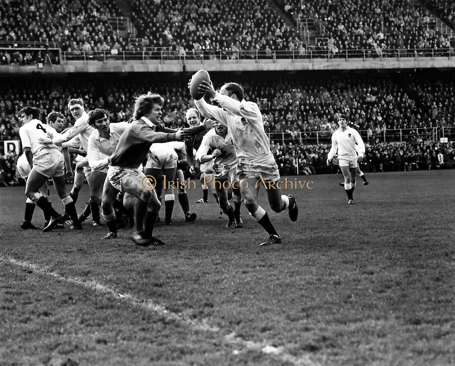 Ireland take on England in the Five Nations Championship at Lansdowne Road. The final score was Ireland 6, England 9. Bob Hiller, the England Fullback, scored all his team's points with three penalties. Ireland replied with two tries from Grant and Duggan. Here an England attacker tries to bypass Fergus Slattery in an attempt to gain ground.<br /> 13/02/1971