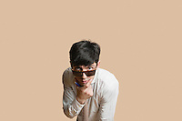Portrait of a young man wearing sunglasses with hand on chin over colored background