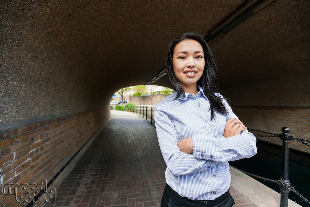 Portrait of confident businesswoman standing arms crossed under bridge