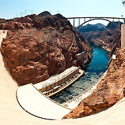 Panoramic shot taken from the top of the Hoover Dam's concrete wall looking down towards the hydroelectric power plant and the Colorando River flowing between the rocky clifs. This is taken from the Nevada side looking towards the Arizona side.