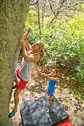Champion climber Robyn Erbesfield-Raboutou bouldering while spotted by her daughter Brooke in Little Cottonwood Canyon, Utah