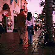 A couple enjoys the twilight as they stroll down State Street in downtown Santa Barbara, California.