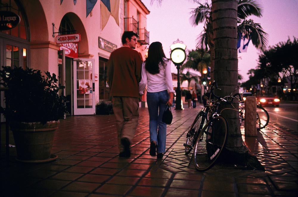 A couple enjoys the twilight as they stroll down State Street in downtown Santa Barbara, California. Photographed for National Geographic Traveler.