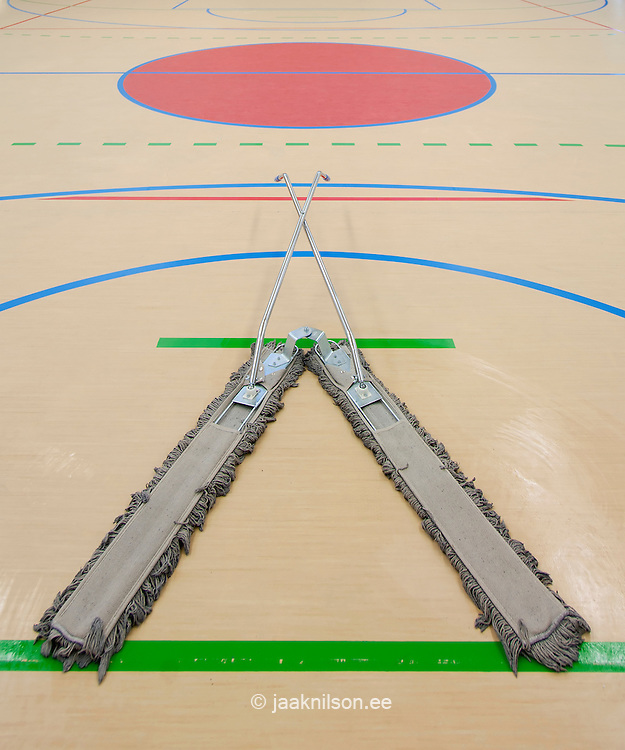 Sports hall and exercise facilities indoors. Gym, basketball court markings. Central circle. Wooden floor. Goal and goal markings for football. Cleaning equipment. Large divided floor sweeper or duster in Metsapoole school, Estonia