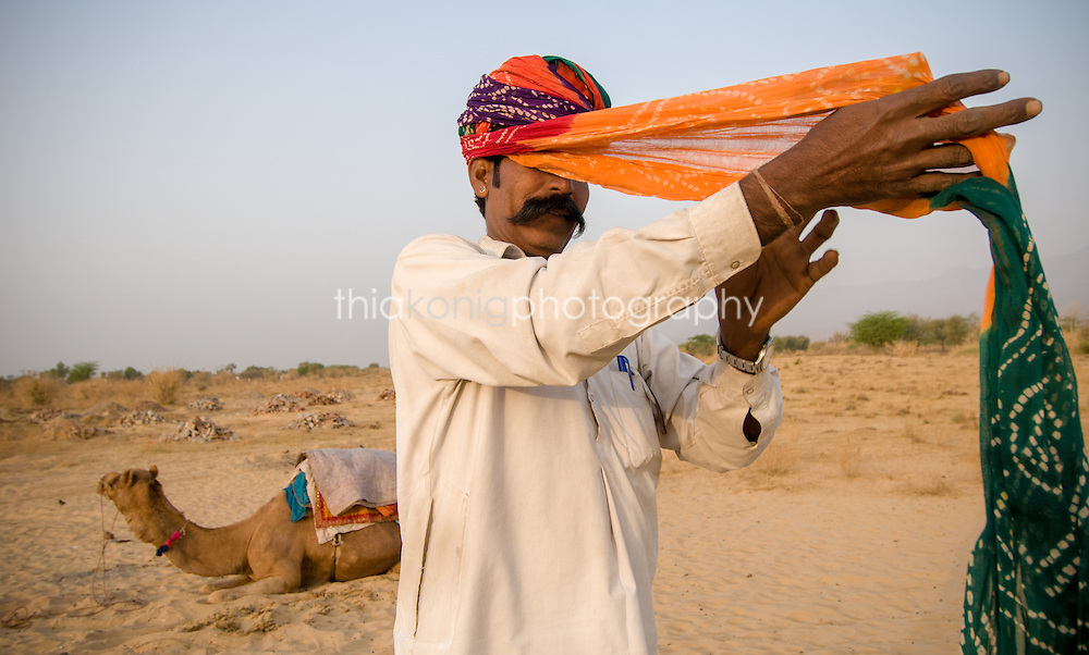 Portrait of camel driver wrapping his turban in the morning light, Pushkar, India, with camel in background.