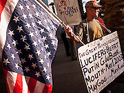 16 MARCH 2011 - PHOENIX, AZ: Jay Schmarle, from Flagstaff, AZ, carries an upside down American flag, an old naval sign of distress, during a protest against former President George W. Bush in Phoenix Wednesday night.   Former president George W. Bush spoke at Arizona Christian University's 50th anniversary dinner at the Phoenix Convention Center Wednesday night. Hundreds of people from progressive and social justice groups demonstrated against the former president.  PHOTO BY JACK KURTZ