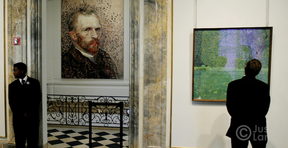 A man (R) looks at Gustav Klimt's 'Pond on Scholss Kammer on the Attersee' with large poster of Vincent van Gogh seen at left at an exhibit exploring the influence of Vincent van Gogh on German and Austrian Expressionism at the Neue Galerie in New York, New York on Wednesday 21 March 2007. The exhibit, which features over 80 major paintings, will be open until 02 July 2007.