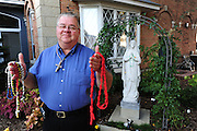 A rosary maker holds a variety of handmade rosaries.