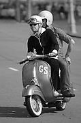 Two scooterists riding on a Vespa, UK 2006