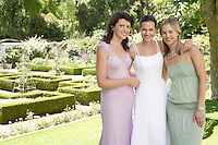 Bride with two women in garden embracing smiling portrait