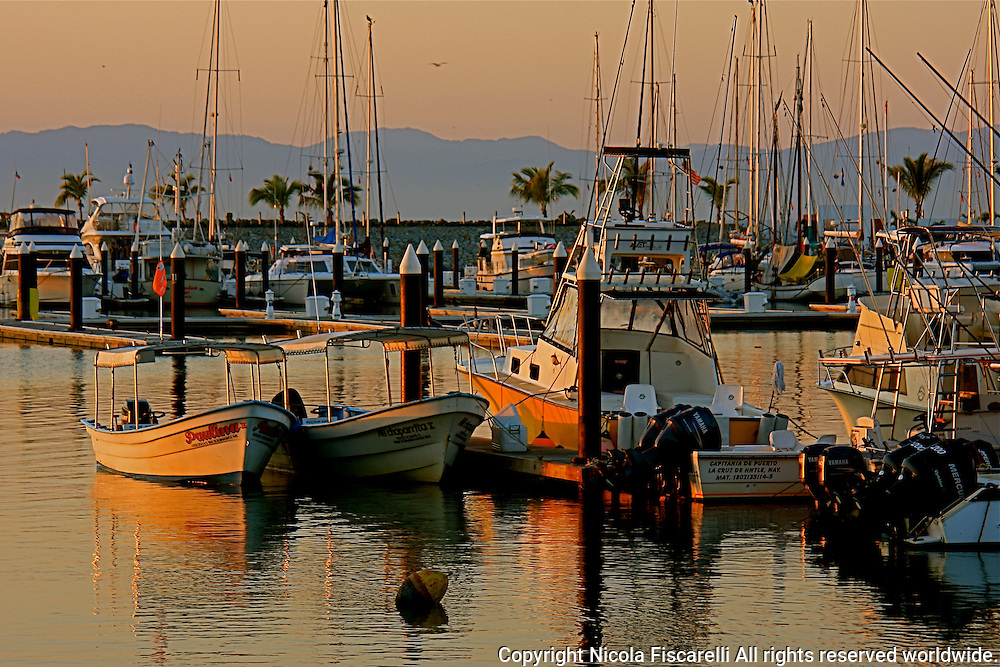 Day break at the La Cruz Marina Mexico and  colorful   water reflections of fishing boats.