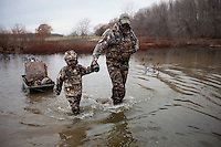 DUCK HUNTER AND YOUNG BOY WADING THROUGH A WETLAND RETRIEVING DECOYS