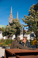 Our Lady of Chartres Cathedral, Chartres, France. Sculpture of  Man posing at a metal picnic table in the town.