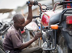 30 May 2019, Mokolo, Cameroon: A man repairs a motorcycle in the marketplace area of Minawao. Today is market day, and refugees and host communities alike gather to sell and buy goods in Minawao. The Minawao camp for Nigerian refugees, located in the Far North region of Cameroon, hosts some 58,000 refugees from North East Nigeria. The refugees are supported by the Lutheran World Federation, together with a range of partners.