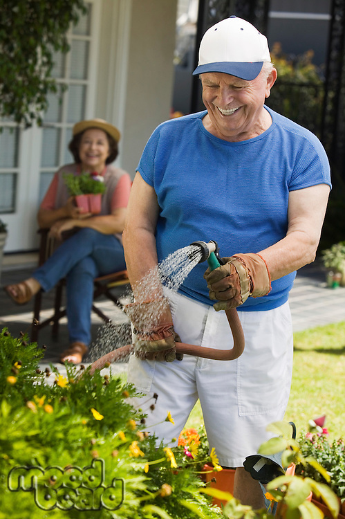 Senior Man Watering the Garden