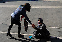 A woman gives some spare change to another woman who is begging outside a church in Rome, Italy