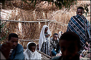 """Tesfaoun and Buzunesh (middle), of ages 6 and 5, are being married. In some cultures, arranged marriage is a tradition handed down through many generations. Parents who take their son or daughter's marriage into their own hands have themselves been married by the same process. Child marriages are typically made for economic or political reasons. North West of Ethiopia, on monday, Febrary 16 2009.....In a tangled mingling of tradition and culture, in the normal place of living, in a laid-back attitude. The background of Ethiopia's """"child brides"""", a country which has the distinction of having highest percentage in the practice of early marriages despite having a law that establishes 18 years as minimum age to get married. Celebrations that last days, their minds clouded by girls cups of tella and the unknown for the future. White bridal veil frame their faces expressive of small defenseless creatures, who at the age ranging from three to twelve years shall be given to young brides men adults already...To protect the identities of the recorded subjects names and specific places are fictional."""