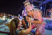 22 NOVEMBER 2013 - BANGKOK, THAILAND: A performer with the Prathom Bunteung Silp mor lam troupe greets a fan during a performance in Bangkok. Although the show is scripted, performers leave their place in the show to go down and greet fans throughout the show. Mor Lam is a traditional Lao form of song in Laos and Isan (northeast Thailand). It is sometimes compared to American country music, song usually revolve around unrequited love, mor lam and the complexities of rural life. Mor Lam shows are an important part of festivals and fairs in rural Thailand. Mor lam has become very popular in Isan migrant communities in Bangkok. Once performed by bands and singers, live performances are now spectacles, involving several singers, a dance troupe and comedians. The dancers (or hang khreuang) in particular often wear fancy costumes, and singers go through several costume changes in the course of a performance. Prathom Bunteung Silp is one of the best known Mor Lam troupes in Thailand with more than 250 performers and a total crew of almost 300 people. The troupe has been performing for more 55 years. It forms every August and performs through June then breaks for the rainy season.     PHOTO BY JACK KURTZ
