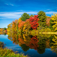 Colorful reflections of foliage on water in Ashland, New Hampshire. <br />