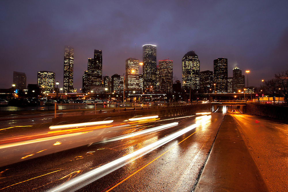 Houston, Texas skyline at night with building lights and light trails- of vehicles on freeway in foreground.