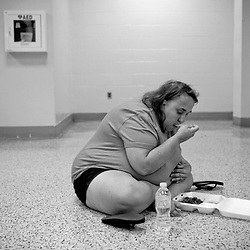 Kyle Green / The Roanoke Times<br /> 7/2/2012 Jennifer Masker eats a meal from The Salvation Army on the floor of a Mass Feeding Center in the Exhibit Hall of the Roanoke Civic Center. Jennifer, who is unable to afford a hotel, has been living at the Red Cross overnight shelter at the Roanoke Civic Center Special Events Center since it opened after Fridays &quot;derecho&quot; storm knocked out power for much of Roanoke, Virginia.