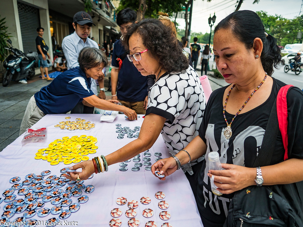 17 OCTOBER 2016 - BANGKOK, THAILAND: Women buy pins with portraits of Bhumibol Adulyadej, the late King of Thailand, for sale near Sanam Luang in central Bangkok. Thai King Bhumibol Adulyadej died Oct. 13, 2016. He was 88. His death comes after a period of failing health. Bhumibol Adulyadej, was born in Cambridge, MA, on 5 December 1927. He was the ninth monarch of Thailand from the Chakri Dynasty and is also known as Rama IX. He became King on June 9, 1946 and served as King of Thailand for 70 years, 126 days. He was, at the time of his death, the world's longest-serving head of state and the longest-reigning monarch in Thai history.        PHOTO BY JACK KURTZ