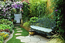 Seating area by the house. Stepping stones in lawn, clematis covered arch, grass border backed by bamboo fence. Brick edging to lawn and metal bench with cushion