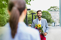 Portrait of young attractive man holding boquet of flowers for his girlfriend in park