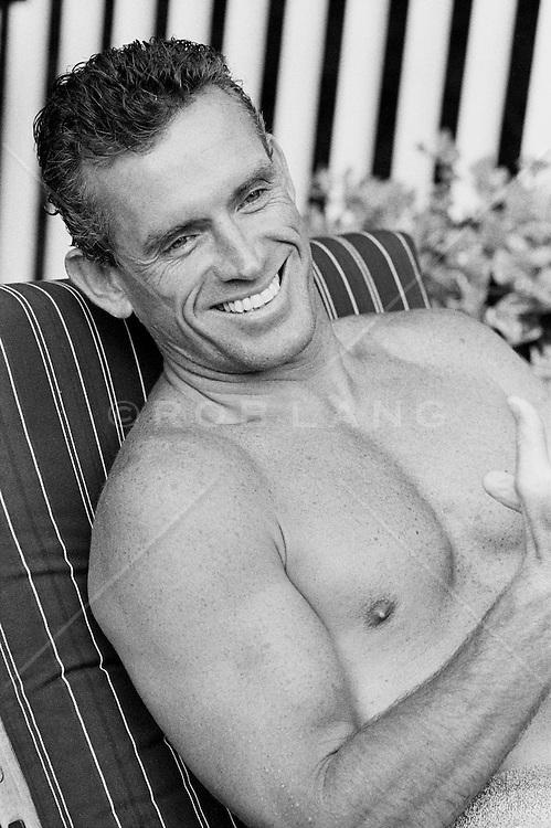 Shirtless man smiling on a lounge chair