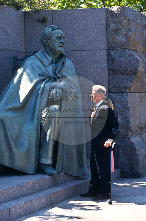 President Bill Clinton and First Lady Hillary pause to view the sculpture of Franklin D. Roosevelt after the opening ceremony of the FDR Memorial May 2, 1997 in Washington, DC. The memorial to the US 32nd president spreads across four granite-walled outdoor rooms along a 7.5 acre-swath of West Potomac Park.