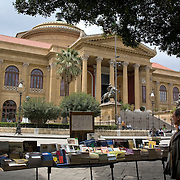 Man looking at books on bookseller's table set up on sidewalk in front of Teatro Massimo, Palermo, Sicily, Italy
