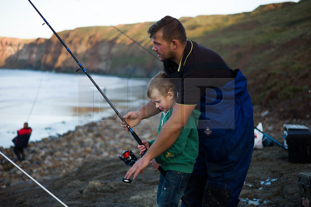 © Licensed to London News Pictures. <br /> 12/10/2014. <br /> <br /> Saltburn, United Kingdom<br /> <br /> Brad Morris from Redcar helps his son, Alfie, 4, during the annual Jim Maidens memorial beach fishing competition in Saltburn by the Sea in Cleveland. <br /> The competition is held each year to mark the death of Saltburn plumber and keen fisherman Jim Maidens who died in 1998 when he was killed after being swept overboard from his boat 'Corina' close to the beach at Saltburn.<br /> <br /> Photo credit : Ian Forsyth/LNP