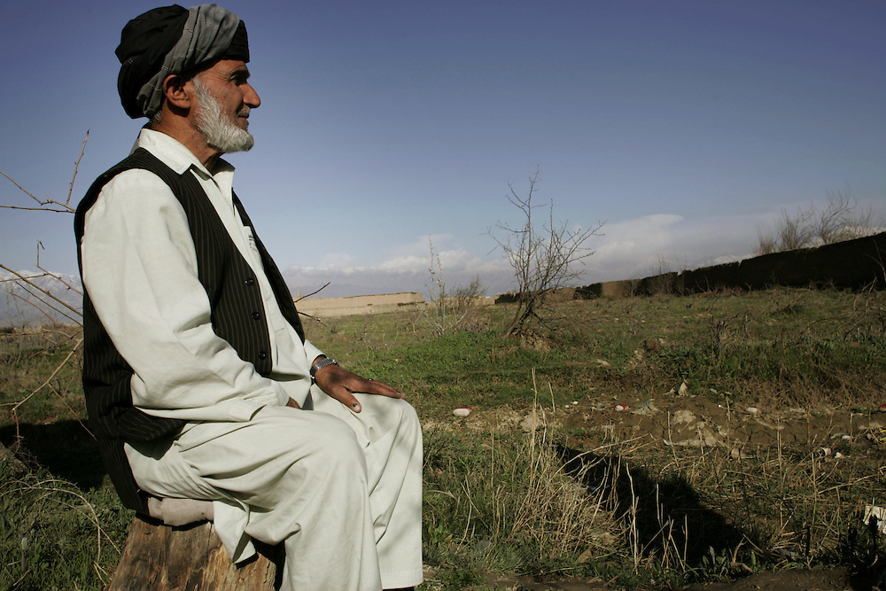 The father of a family sits by land that he is preparing to plant potatoes in for the first time in an area that was recently cleaned of mines.