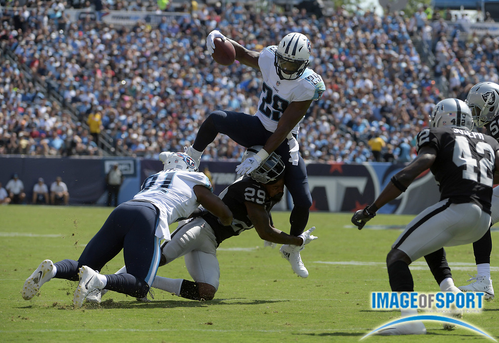 Sep 10, 2017; Nashville, TN, USA; Tennessee Titans running back DeMarco Murray (top) leaps over Oakland Raiders cornerback David Amerson (bottom) during a NFL football game at Nissan Stadium. The Raiders defeated the Titans 26-16.