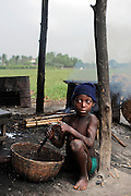 A young boy is preparing fish for drying on wooden handmade racks in Cotonou, Benin March 1, 2008.